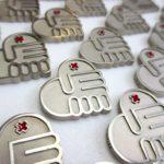 Pins voor het Rode Kruis uitgevoerd in alpaca en met emaille