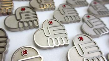 Pins voor 150 jaar behulpzaamheid bij het Rode Kruis