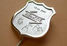 Grote speld van goud en zilver met logo en symboliek